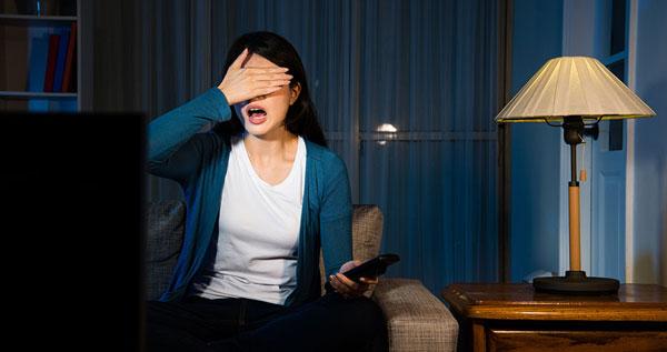 Chica viendo la televisión a oscuras