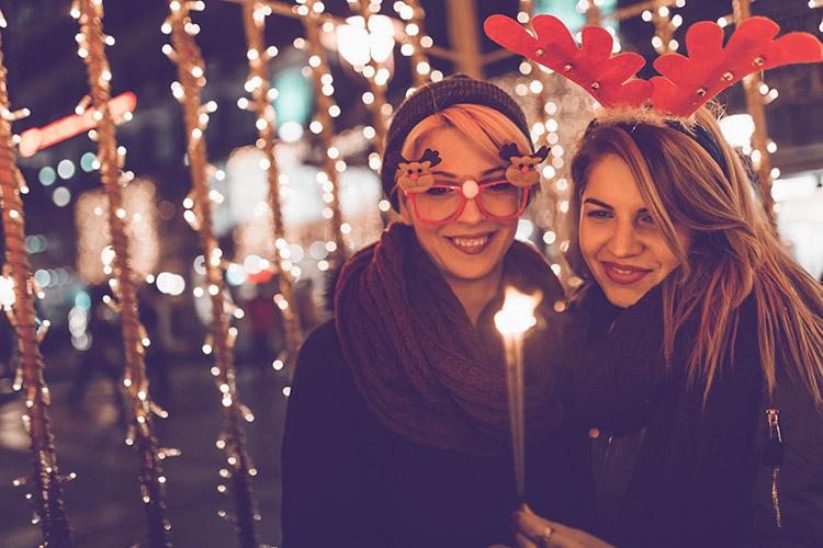 Chicas en la calle iluminadas por las luces de Navidad