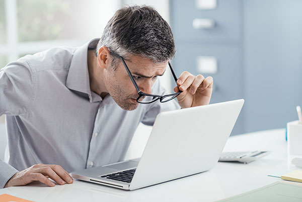 Hombre con hipermetropía ajustando visión al ordenador