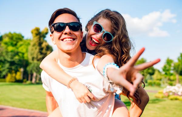 Salud Visual, niveles de protección. Una pareja feliz en el parque con gafas de sol