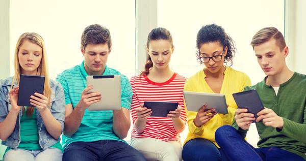 Jóvenes con móviles, portátiles, pantallas, tablets